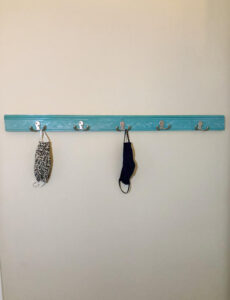 A DIY face mask rack made with double coat hooks, pretty chair rail molding, and spray painted a beautiful blue green