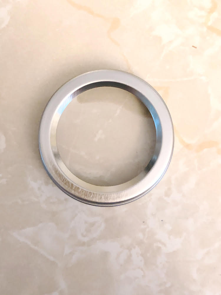 clear lid of a magnetic spice tin on a laminate countertop