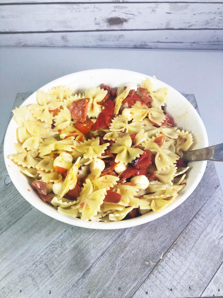 a bowl of pasta salad with roasted red peppers, salami and mozzarella pearls