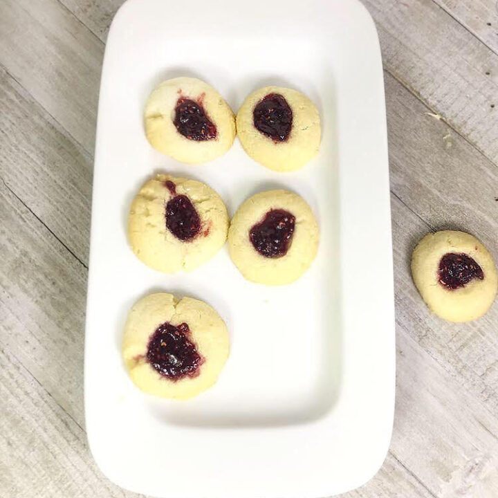 raspberry thumbprint cookies on a rectangular plate