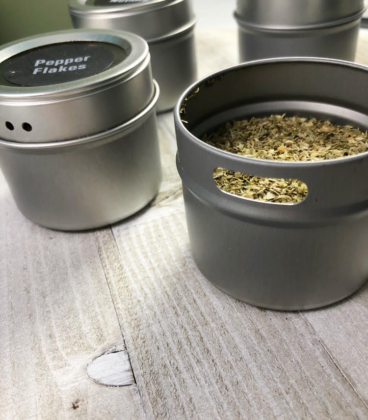 refillable magnetic spice tins, one filled with oregano and one filled with red pepper flakes