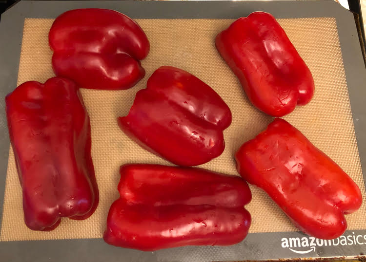 red peppers on a silicone baking mat to be roasted in the oven