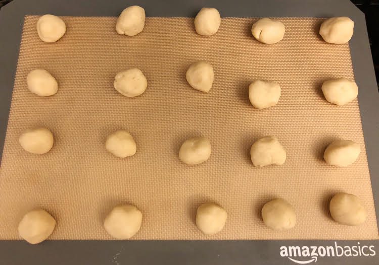 Balls of shortbread cookie dough on a silicone baking mat on a cookie sheet