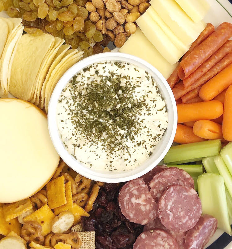 garlic and herb soft Alouette Cheese on a charcuterie board with meats, celery and carrot sticks, peanuts, raisins and potato chips