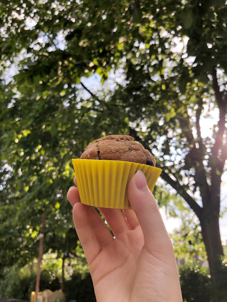 hand holding banana muffin in a pretty yellow reusable silicone cupcake linter