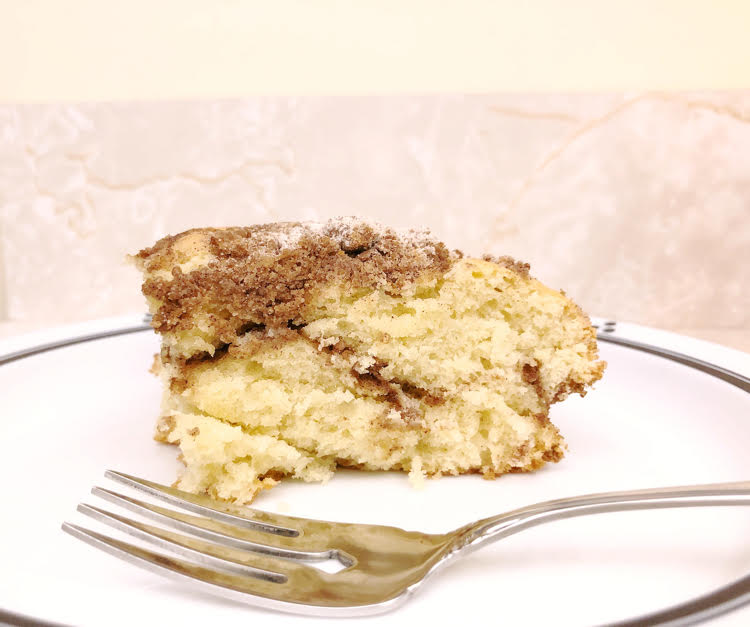 a piece of cinnamon crumb cake on a white plate with a fork