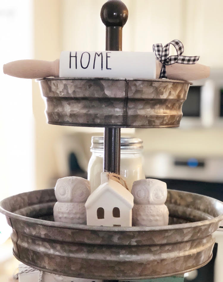 "a cute tiered tray in a kitchen, decorated with a mini ""home"" rolling pin, white owl salt and pepper shakers and a white ceramic mini house"