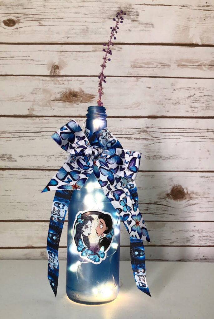 DIY decorated blue wine bottle in a Corpse Bride theme