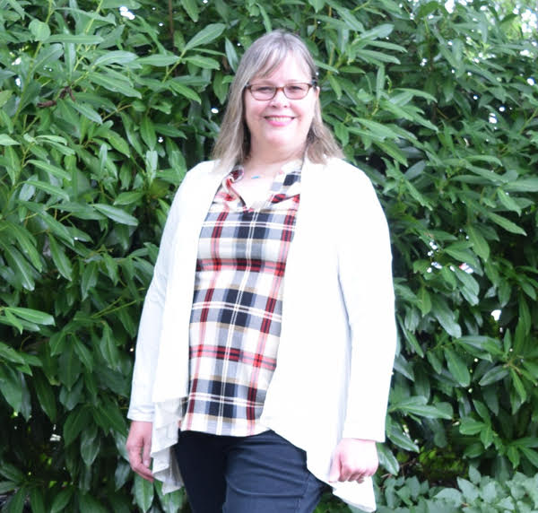 woman wearing white cardigan, plaid top and dark wash jeans