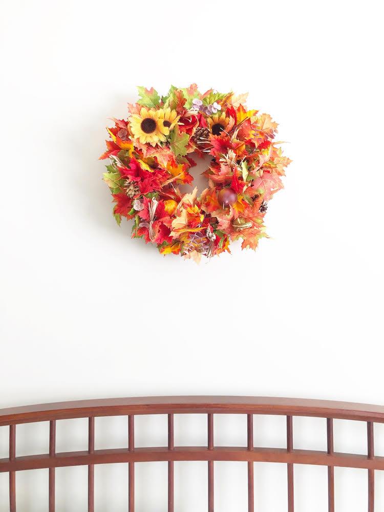 Fall leaf wreath over a farmhouse-style bed