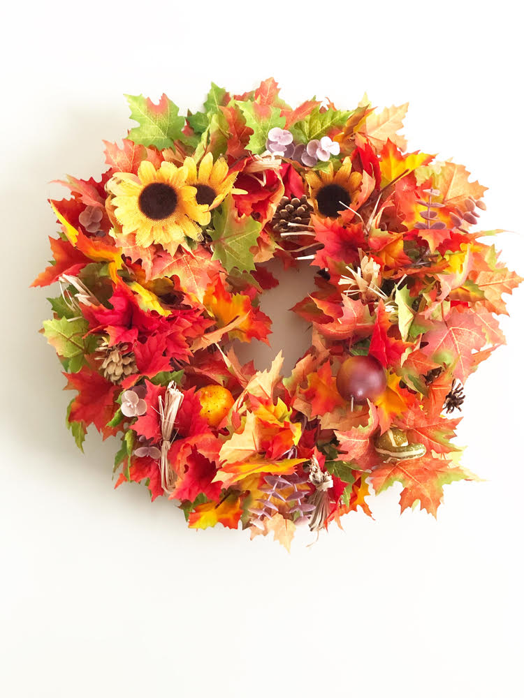 a beautiful fall leaf wreath with sunflower accents