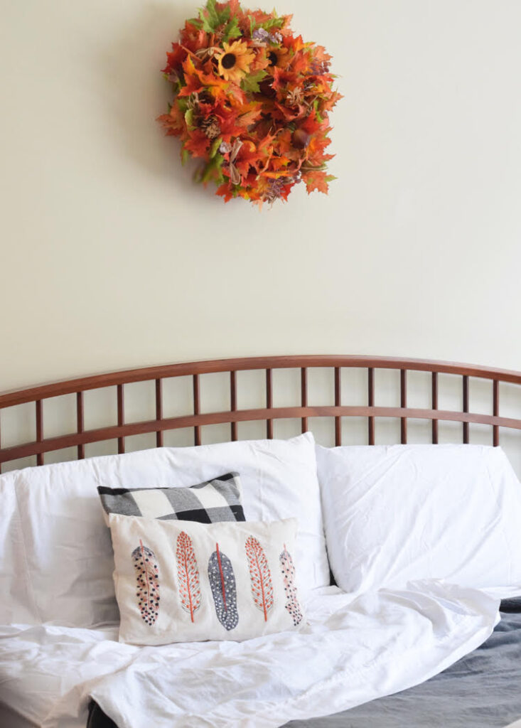 farmhouse style bed with a cozy gray plush Therapedic blanket, white sheets and a fall leaf wreath on the wall