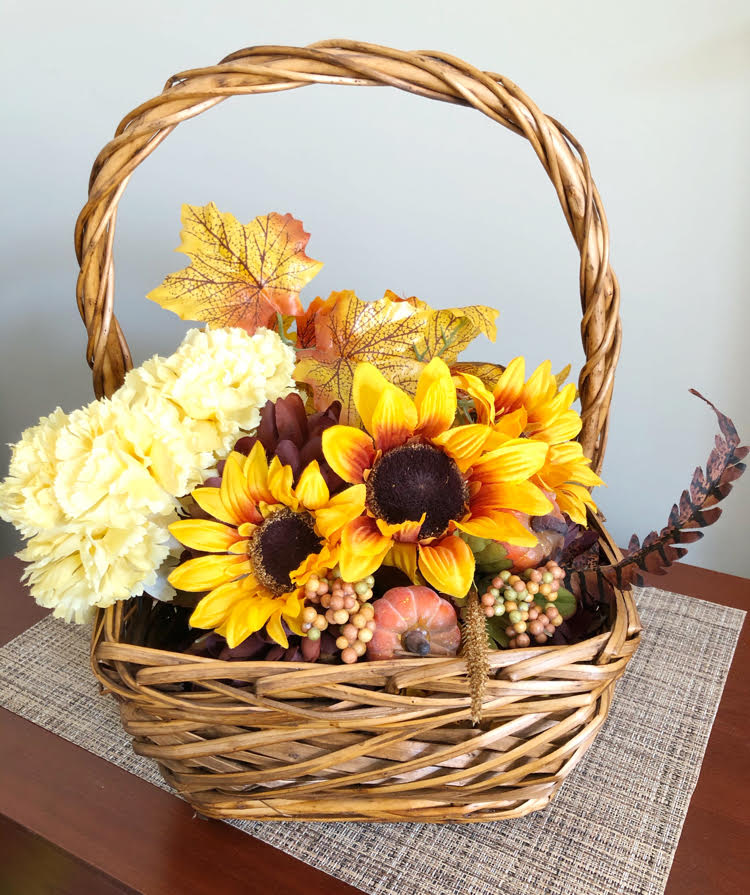 A faux floral arrangement in a basket with silk fall leaves, mini pumpkins and sunflowers
