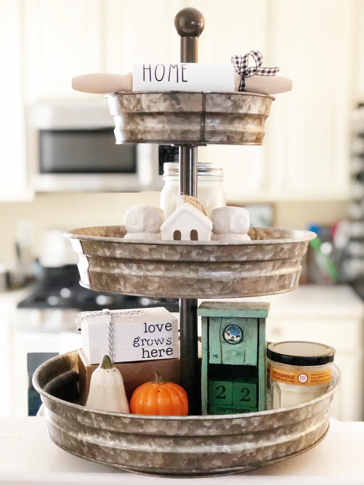 "a galvanized 3-tier tray in a kitchen. On the tray on owl salt and pepper shakers, pumpkin and squash salt and pepper shakers, a wooden birdhouse calendar, a jarred candles, a ceramic house a mini ""home"" rolling pin and a ""love grows here"" faux book stack."