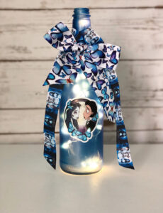 a hand-decorated Corpse Bride wine bottle with a Corpse Bride sticker and ribbons