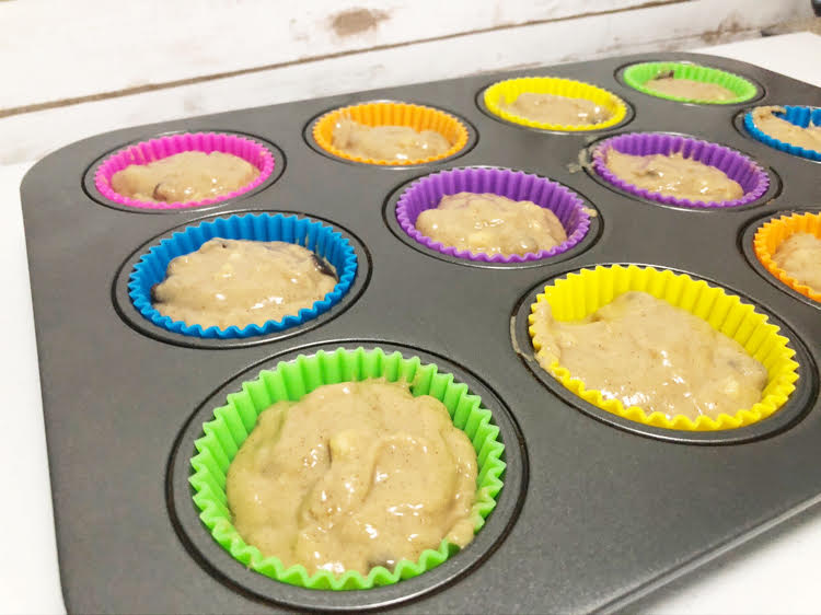 muffin batter in colorful silicone cupcake liners in a muffin tin