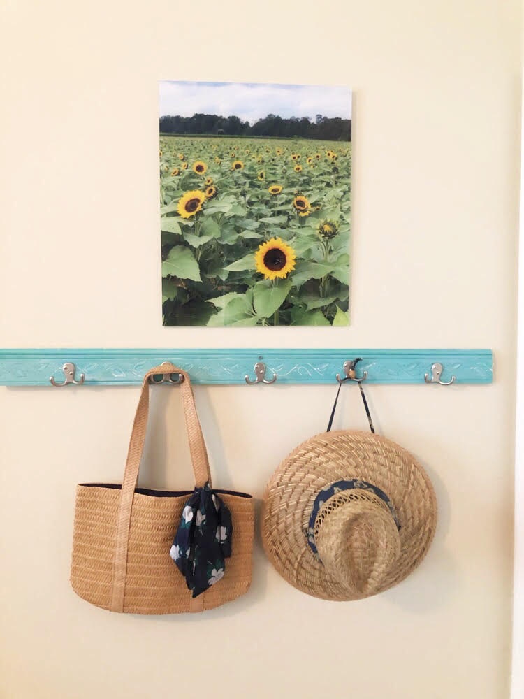 A straw tote and a straw hat hanging on a DIY coat rack under a pretty print of a sunflower field.