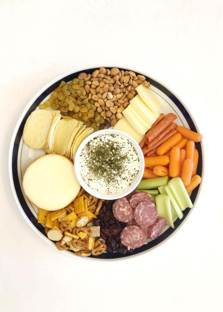 cheeses, salami, carrot and celery sticks, and peanuts on a charcuterie board
