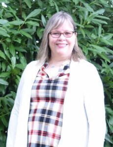 woman wearing a plaid top and white cardigan sweater