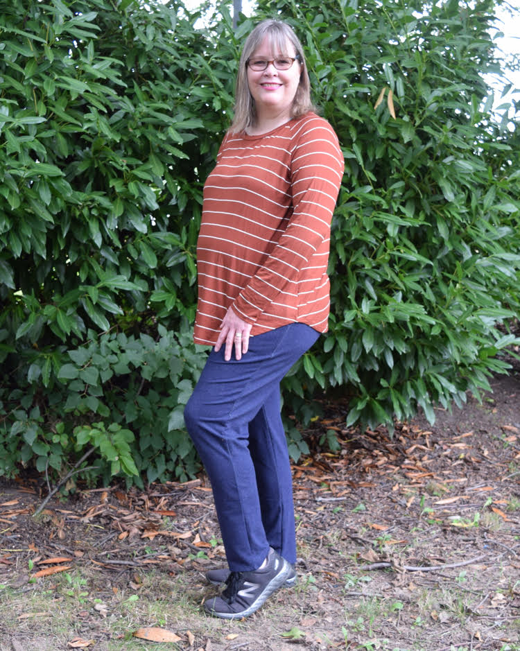 woman wearing an orange shirt with white stripes, and navy sweatpants