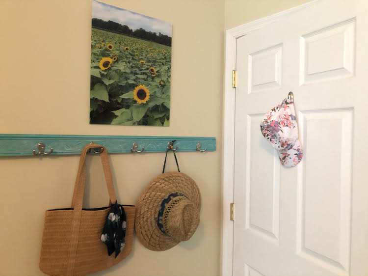 acrylic print of a sunflower field hanging over a coat rack holding a straw bag and hat by a white door