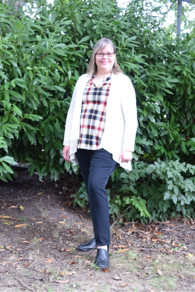 woman wearing plaid top, dark wash jeans and an open white cardigan