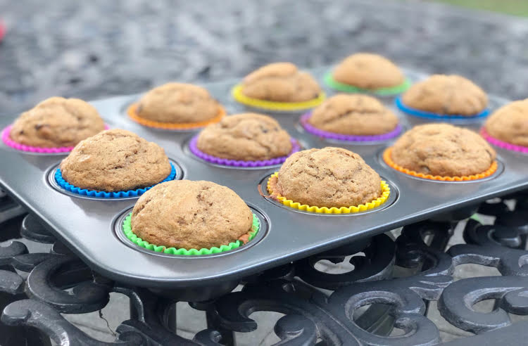 banana chocolate chip muffins in rainbow colored silicone cupcake liners in a muffin tin