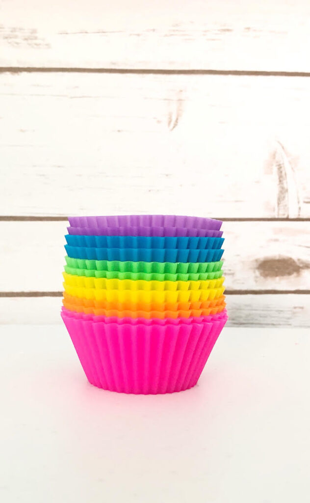 colorful silicone cupcake and muffin liners against a shiplap wall