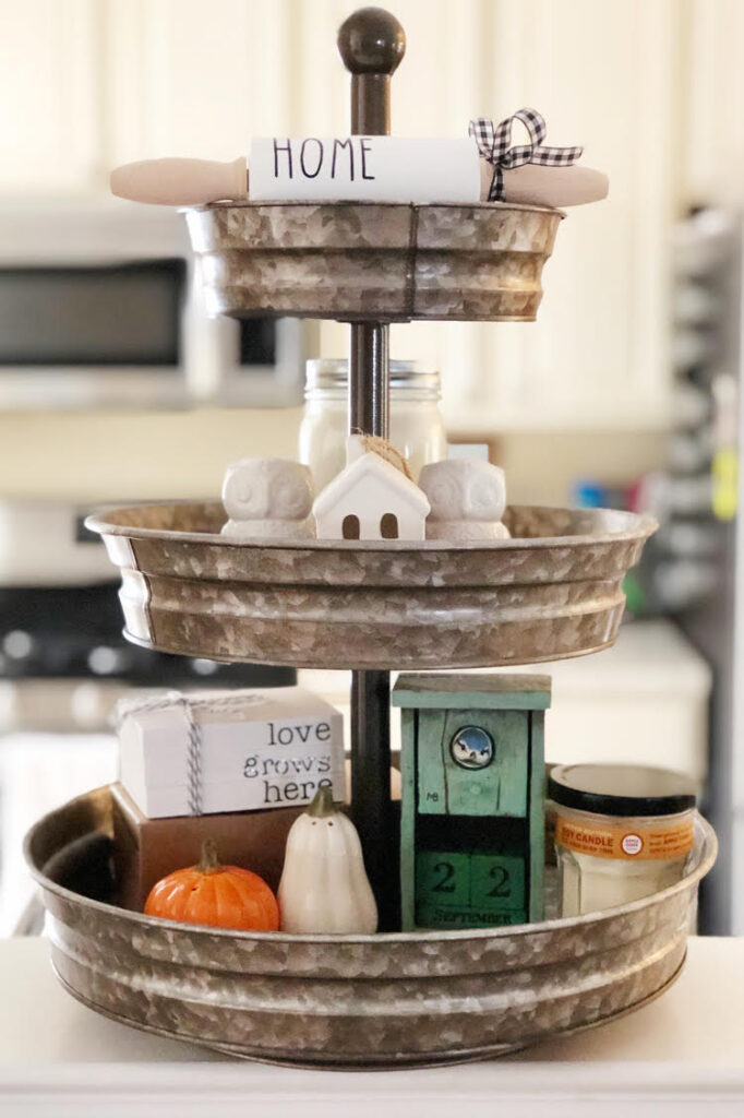 a three tiered galvanized tray filled with decorative salt and pepper shakers, a faux book stack and a mini white ceramic house.