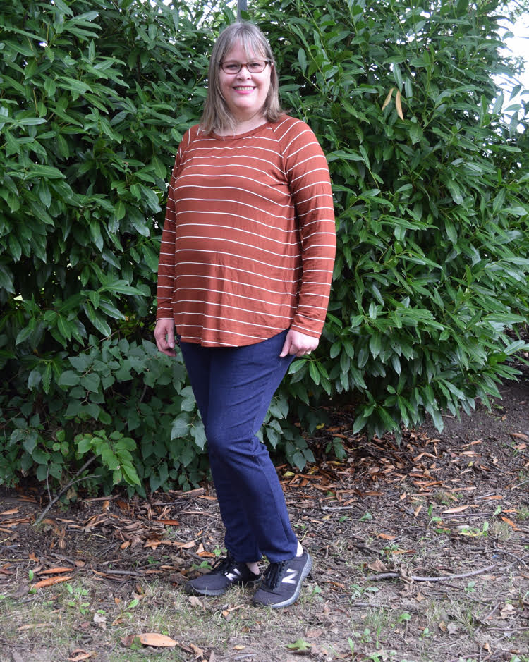 woman wearing an orange top with white stripes and navy blue sweatpants
