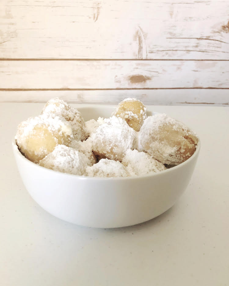 a bowl of air fried dough or zeppole dusted with powdered sugar