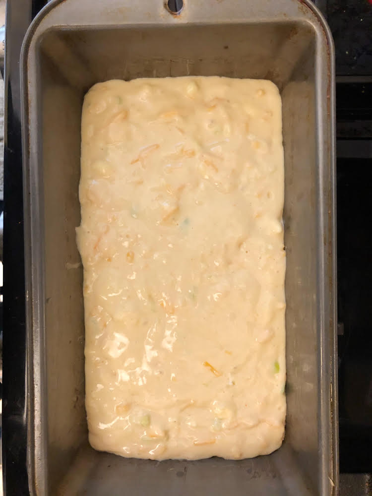 cheddar green onion bread batter in a loaf pan