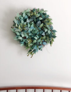 nearly natural faux wreath with green leaves and berries on a wall