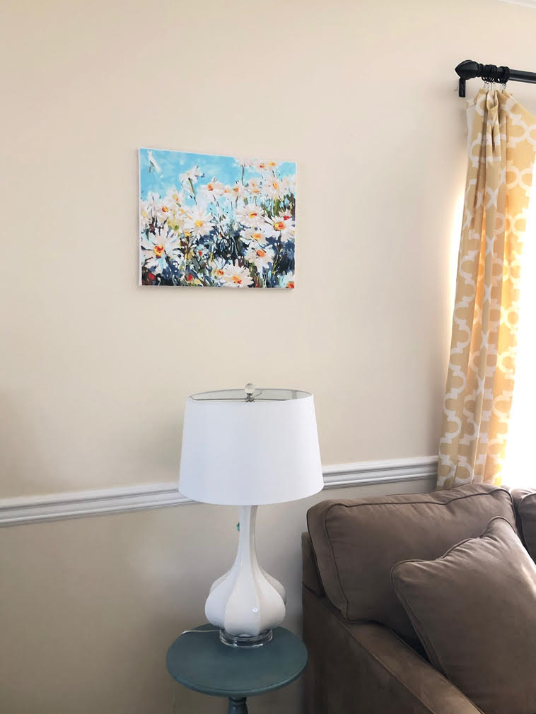 daisies painting on wall in bright and sunny living room