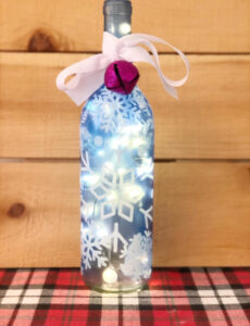 a beautiful DIY lighted wine bottle decorated with snowflakes