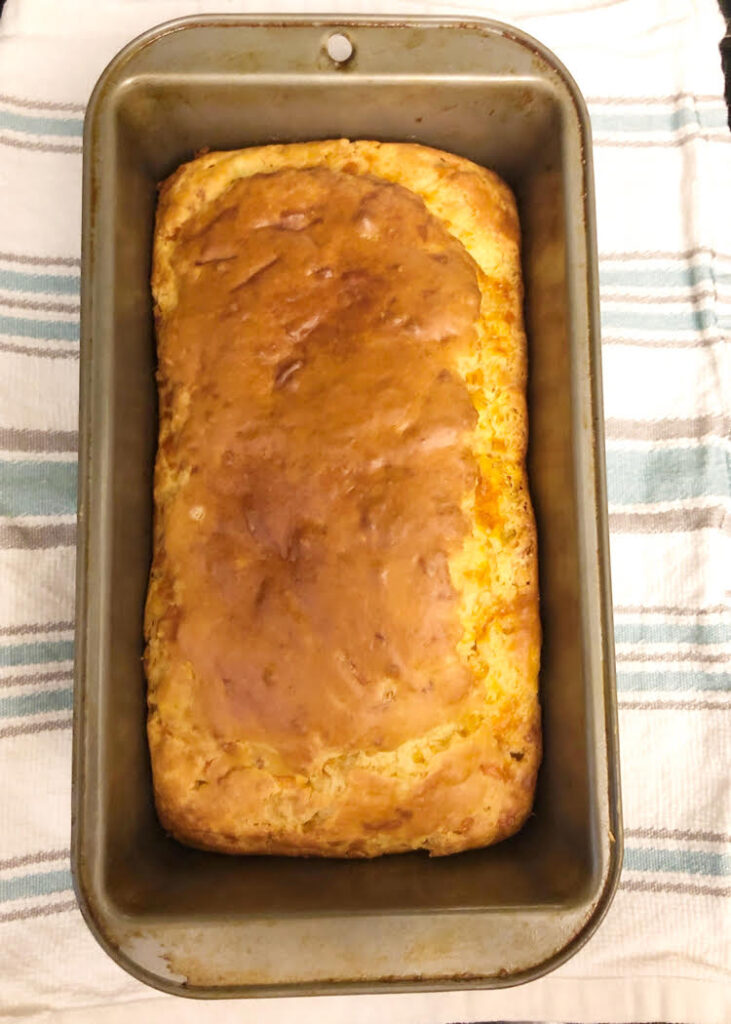 a loaf of homemade cheddar and green onion quick bread in a  loaf pan on a farmhouse style cotton towel