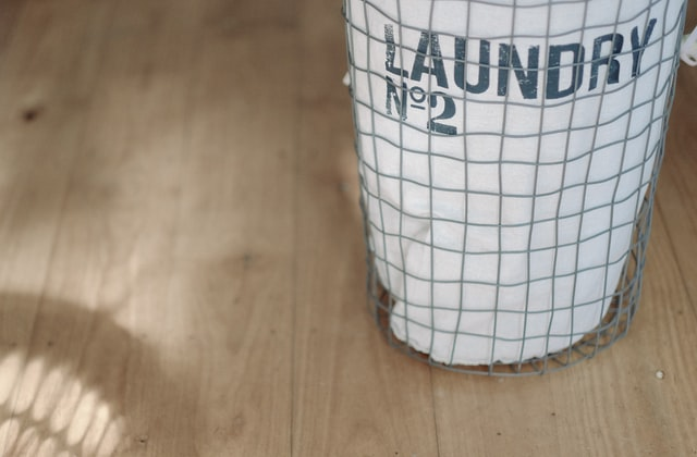 a wire laundry basket with a white laundry bag on a wood floor