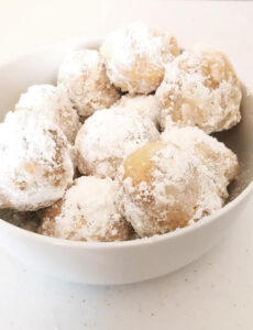 a bowl of fried pizza dough balls (zeppole) dusted with powdered sugar