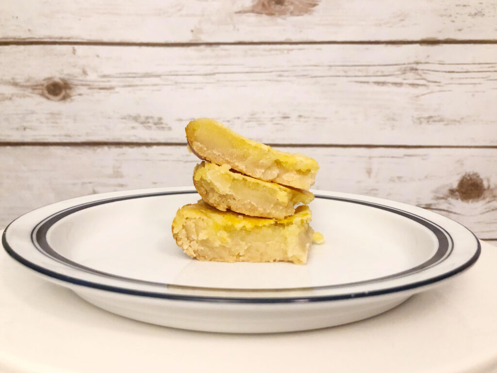 A stack of delicious homemade shortbread lemon bars on a white plate against a plank wall background
