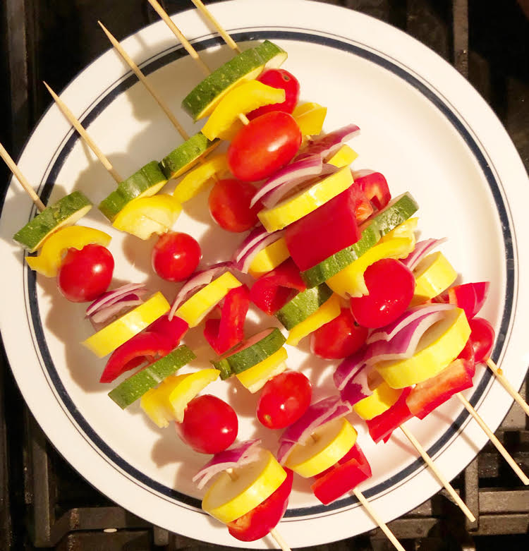 squash, peppers, onion and tomatoes on a wooden skewer for cooking over a fire pit