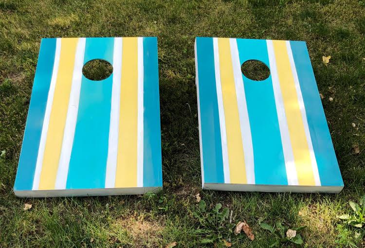 yellow and blue striped cornhole boards