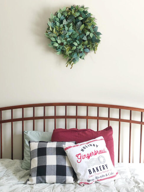 beautiful faux leaves and berries wreath for the Christmas and holiday season over a pretty farmhouse style bed
