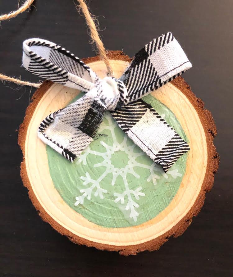 handmade snowflake wood slice ornament with a black and white buffalo plaid bow