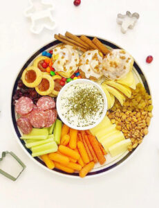 christmas charcuterie tray with cheeses, meats, veggies, dried fruits, cinnamon rolls and candy