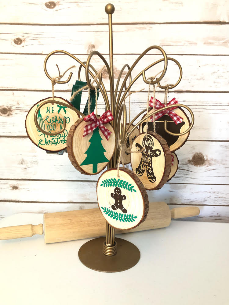 a gold ornament stand with kitchen themed wood slice ornaments.