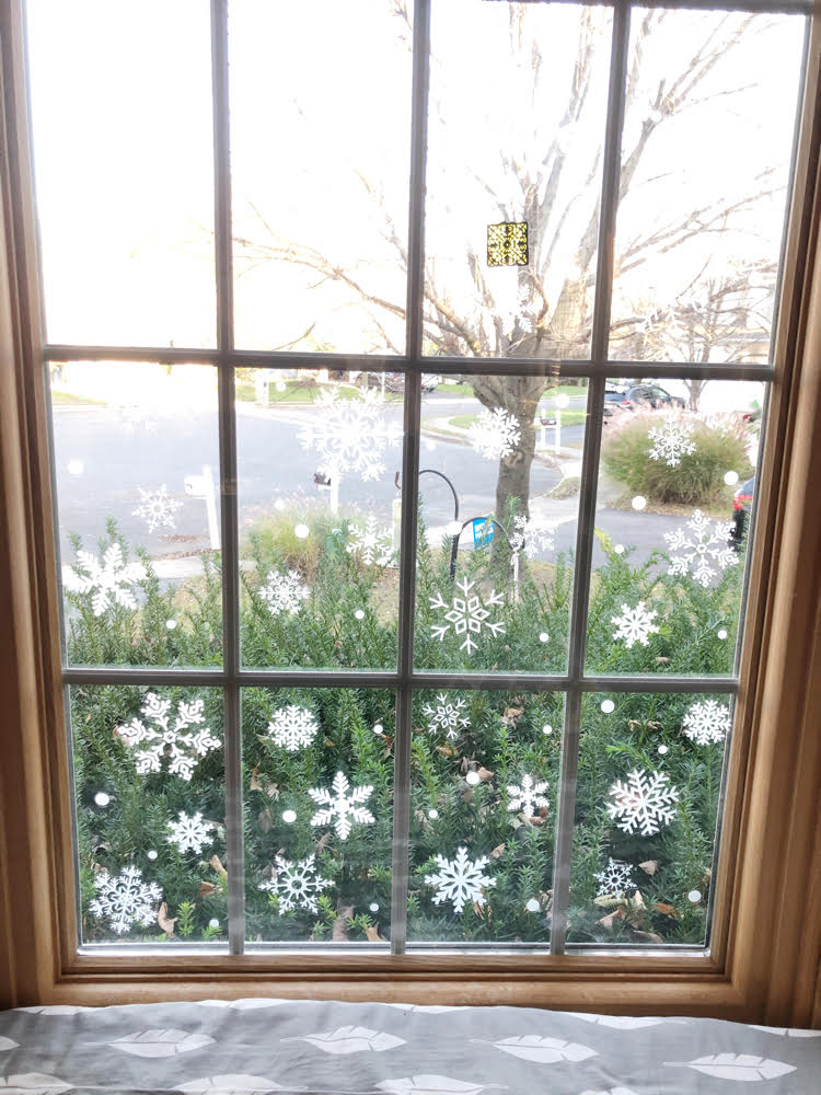 white vinyl snowflakes in a bay window for Christmas