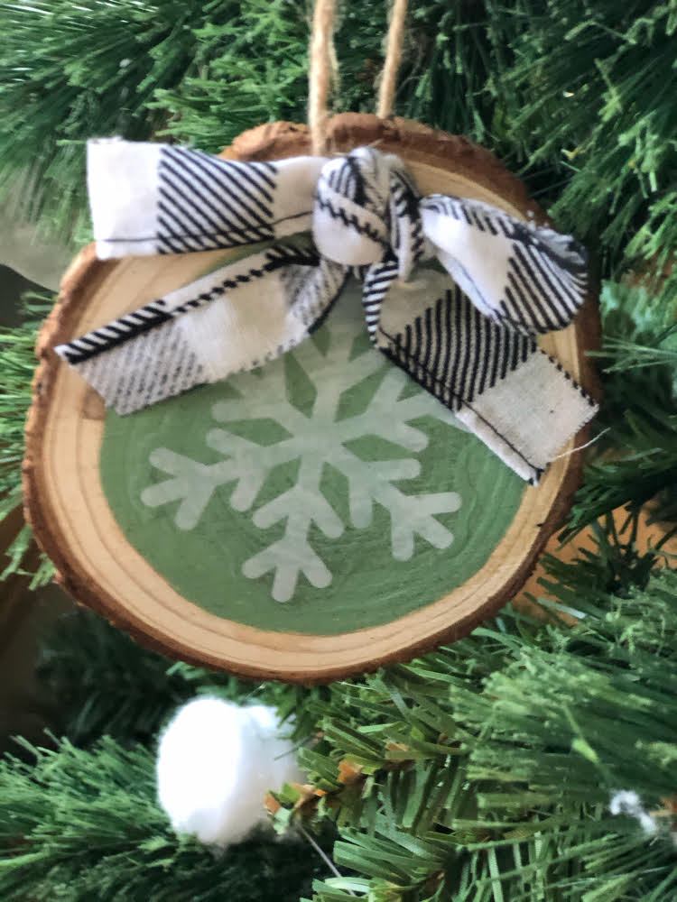 a homemade snowflake wood slice ornament with a black and white buffalo plaid ribbon
