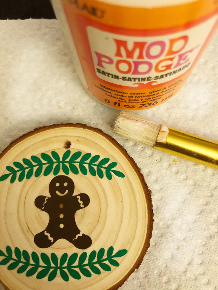 Applying Mod Podge over a vinyl design on a DIY wood slice ornament will help your design to last for as along as you need it