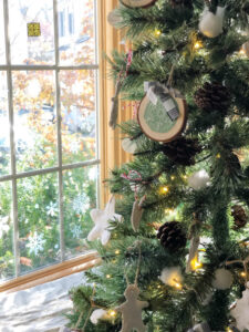 rustic faux christmas tree by a window with snowflake decals