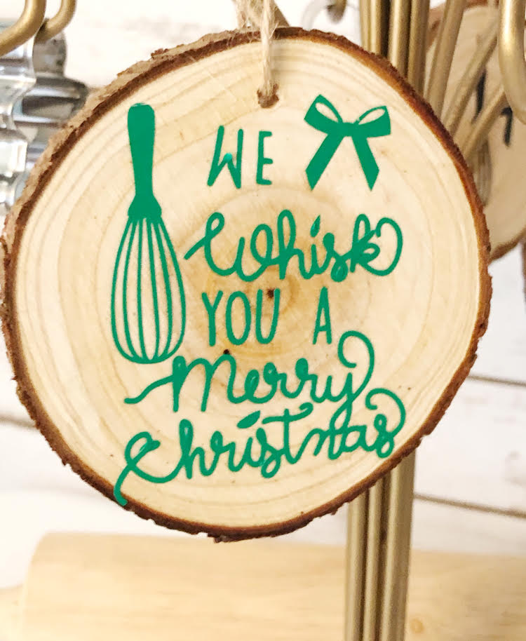 """a homemade """"We Whisk You a Merry Christmas"""" wood slice ornament on an ornament stand"""